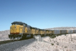 Union Pacific EMD SD-60M 6165 winds around a tight curve in the rugged desert landscape