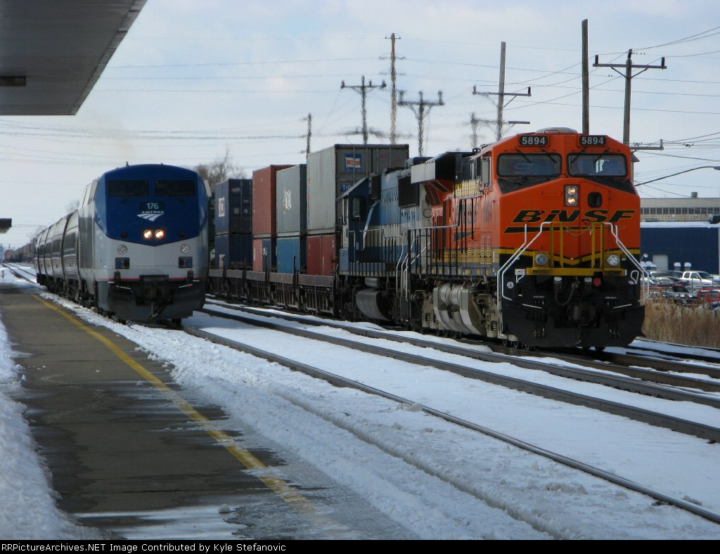 BNSF 5894 pulling past the Maple Leaf who has just made his station stop and is starting to pull