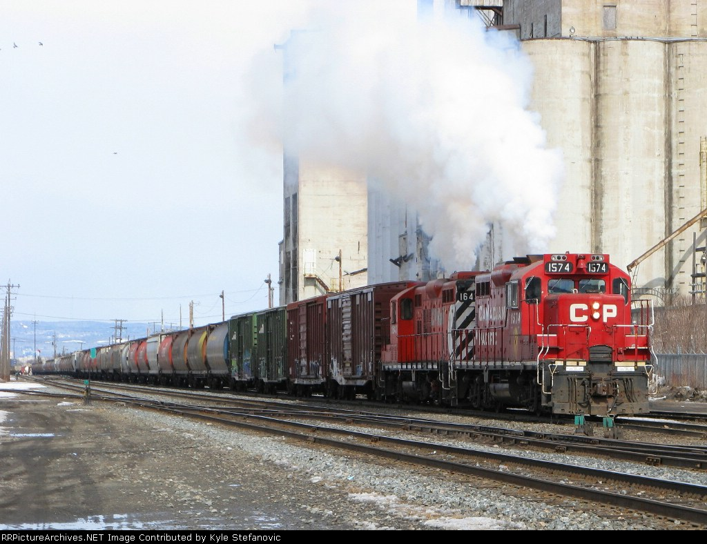 The SMOKE pours out as a pair of CP geeps works hard to pull a cut of 109 cars
