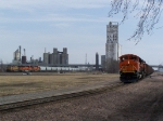 BNSF 9144 Waits While a UP Grain Train Makes its Way To the UP/BNSF Diamond With 2 Shiny New BNSF Swoosh Motors