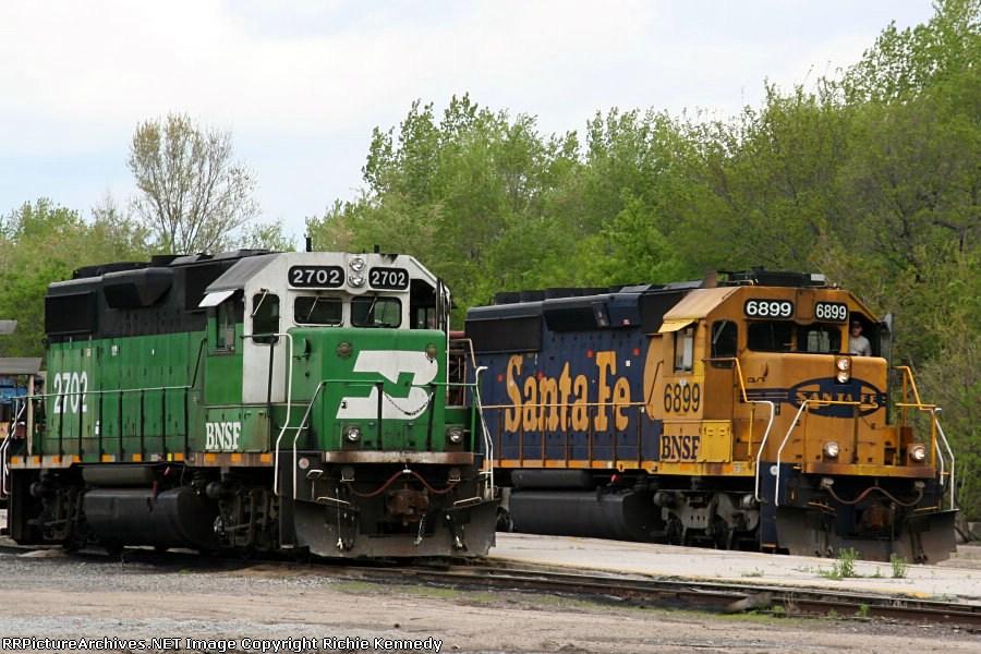 BNSF SD40-2 6899 leads a work train past yard goat 2702.