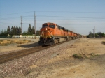BNSF 7782 charges hard by Modesto with a westbound manifest