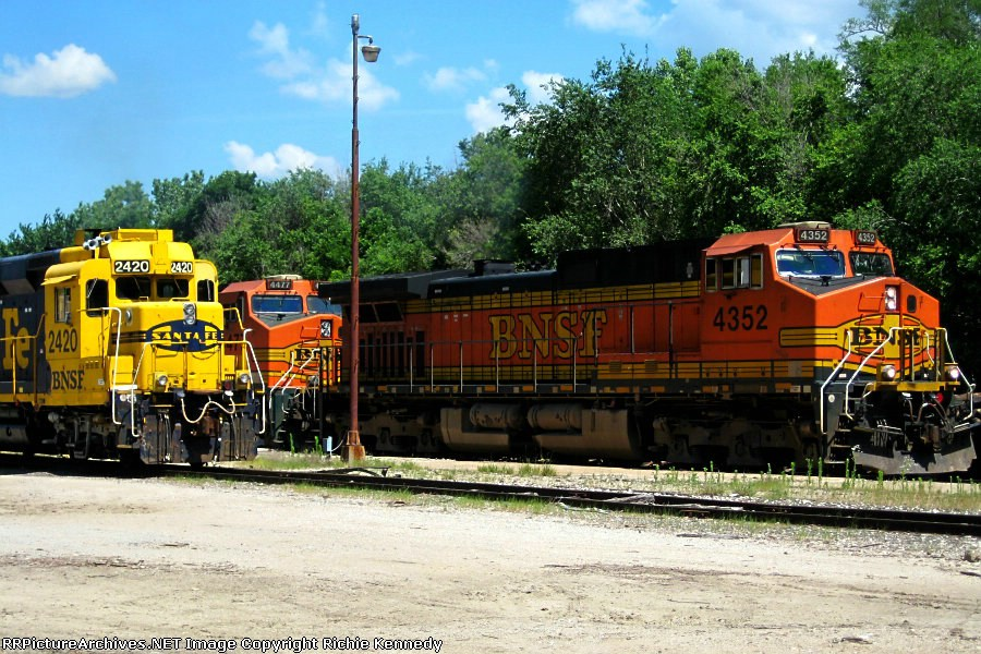 BNSF C44-9W 2352 and 4477 roll past yard goat GP30 2420.