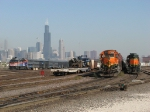 The Chicago skyline looms as an inbound Dinky passes Western Ave Yard