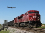 CP 8799 & 8810 get ready to pull as a United 757 passes overhead
