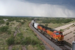 BNSF 4916 coming out of the Canadian river valley while a summer storm showers rain in the distance