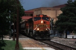 "BNSF C44-9Ws 5067 and 5413 lead an eastbound ""worm"" past the platform of the Lawrence depot"