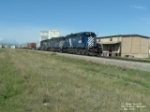 MRL 211 SD40 in front of grain elevators and warehouse