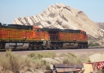 A BNSF train coming up th pass with a neat rock formation behind it