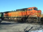 BNSF 5180 sitting in the shadows of trees