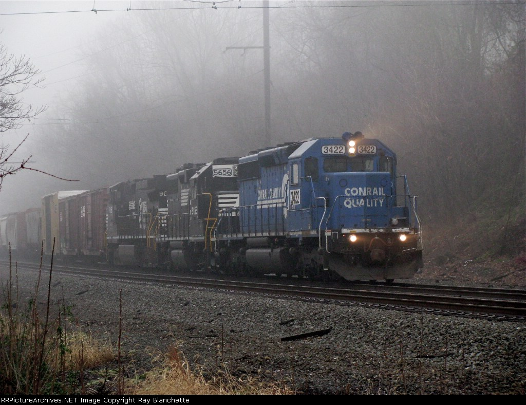 Long NS train headed by Conrail 3422 approaches grade crossing