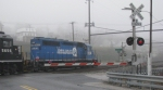 NS 3422 heads train through grade crossing