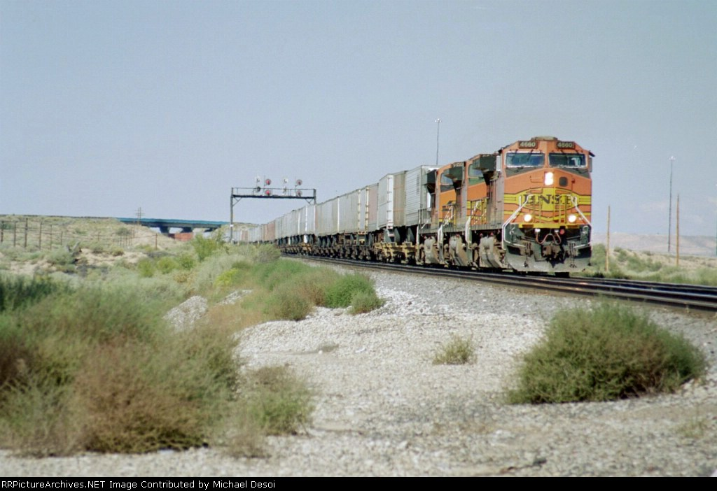 BNSF 4660 brings an eastboud trailer train in under I-25 and across Mesa Rd.
