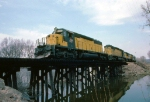 1224-34 Southbound C&NW freight on ex-M&StL mainline crosses trestle over slough next to Minnesota River between Carver and Merriam