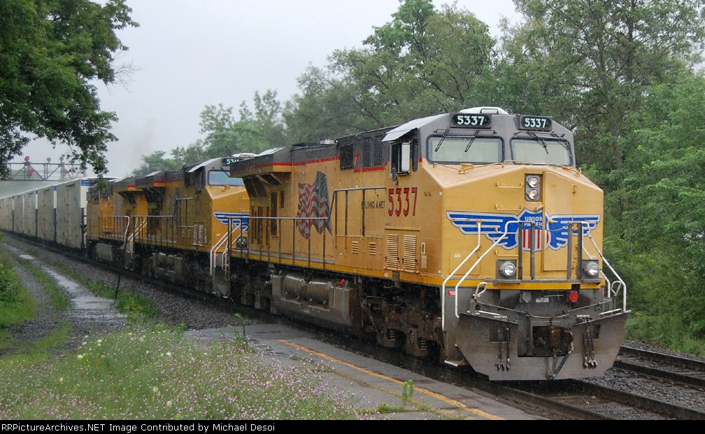 UP 5337 + 2 other Gevos takes empty reefers west in the rain through the passenger station