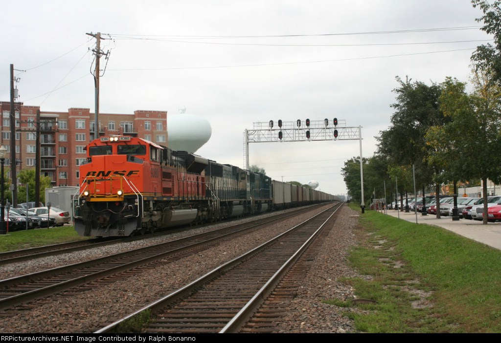 A westbound train of empty hoppers rolls through with two BNSF units and a CSXT SD70AC