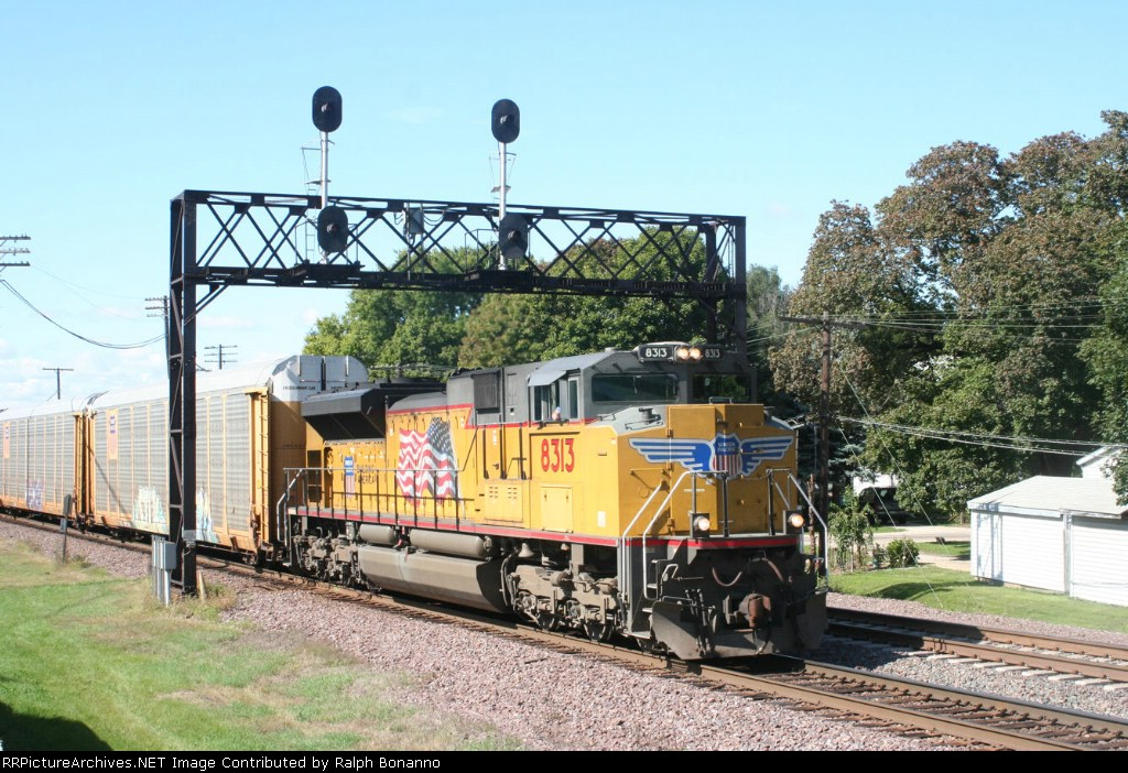 A  single UP SD70ACe leads auto racks eastbound through town and across the BNSF