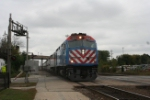 A westbound Metra afternoon local arrives with an F59 leading
