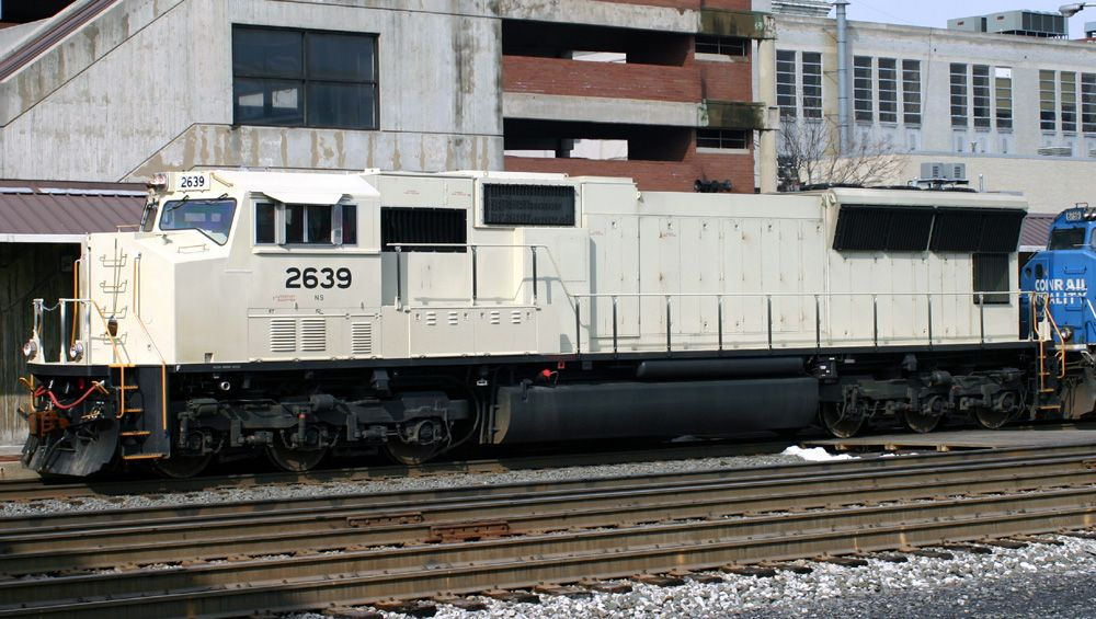 A new SD70M still in primer leads a westbound stack train