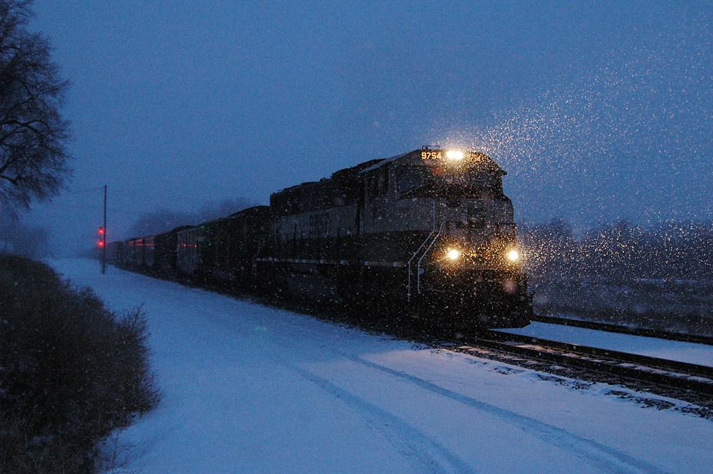 BNSF 9754 with coal loads roll Eastbound through the snow storm
