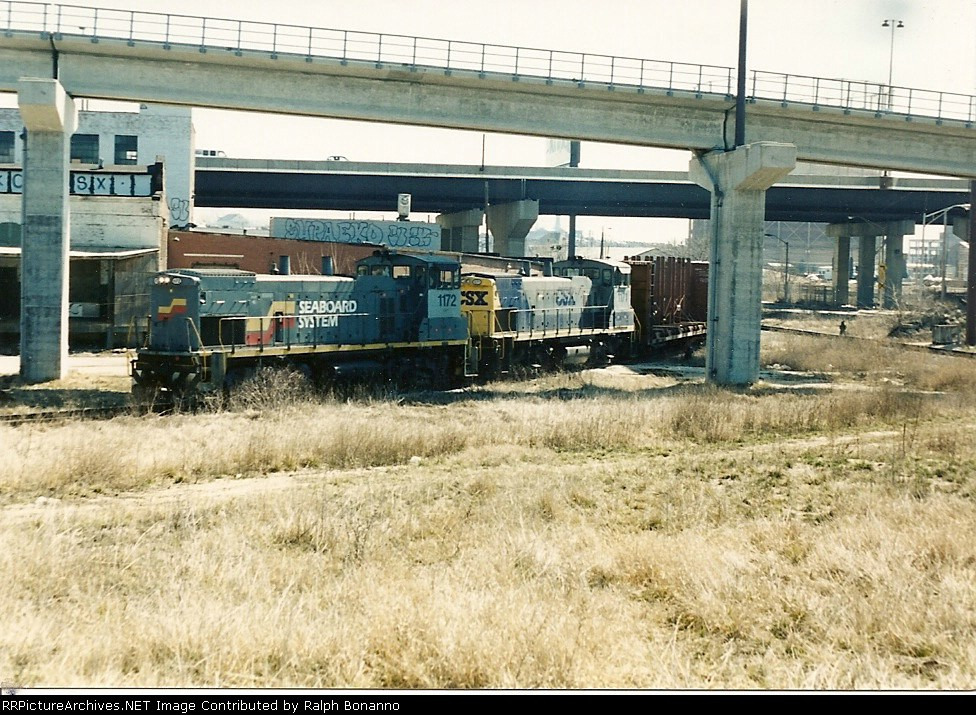 A CSX local winds its way through the city with a apir of MP15ACs in different schemes