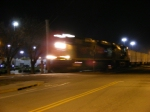 A blurred GEVO leaving town with an empty coal train in tow