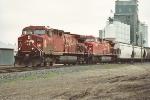 Westbound grain train departs small yard