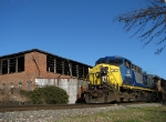 CSX 14 backs past the factories to its train