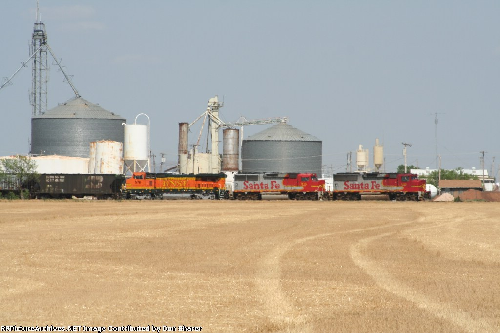 Placing more empties at the silo next to the fresh cut wheat field in near 100 degree heat