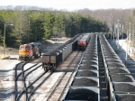 BNSF & KCS power waits near three loaded train sets