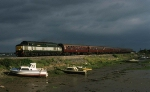 37198 heads for Exeter against a stormy sky