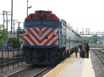 Heading into the city, METX 123 throttles up past waiting passengers