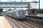 Northbound ACELA express barrells through in the afternoon sun.
