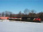 CN 8855 and BCOL 4644 glide southward, slowing to hold the main and let a CP cross the diamond