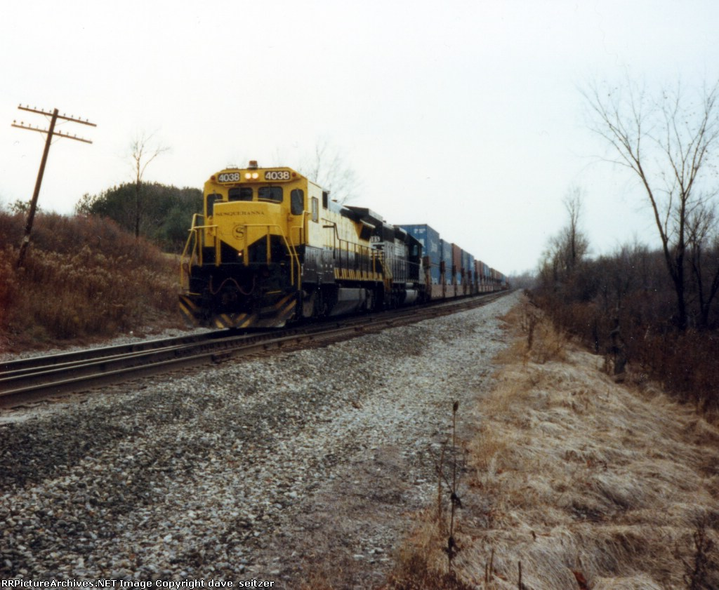 NYSW 4038 and an NS unit lead a Eastbound stack train on Molasses Hill