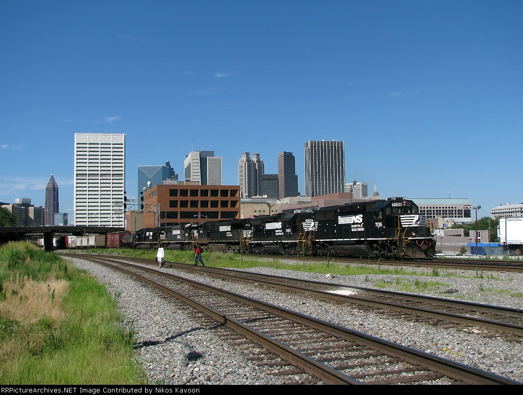 "NS 7136 leads awesome consist past Spring St. while two ""urban outdoorsmen"" wander around on the NS main"