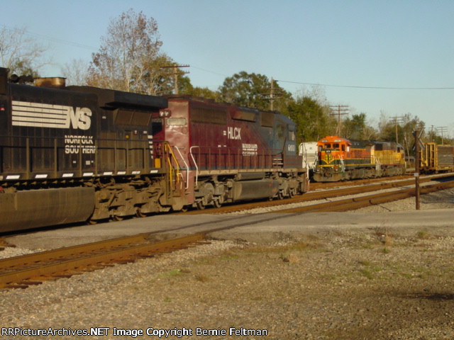 Norfolk Southern C40-9W #9300 and HLCX SD40-2#6100 move down the main southbound as Burlington Northern Santa Fe B40-8 #8636 and Union Pacific SD60 #2218 build their local in the background