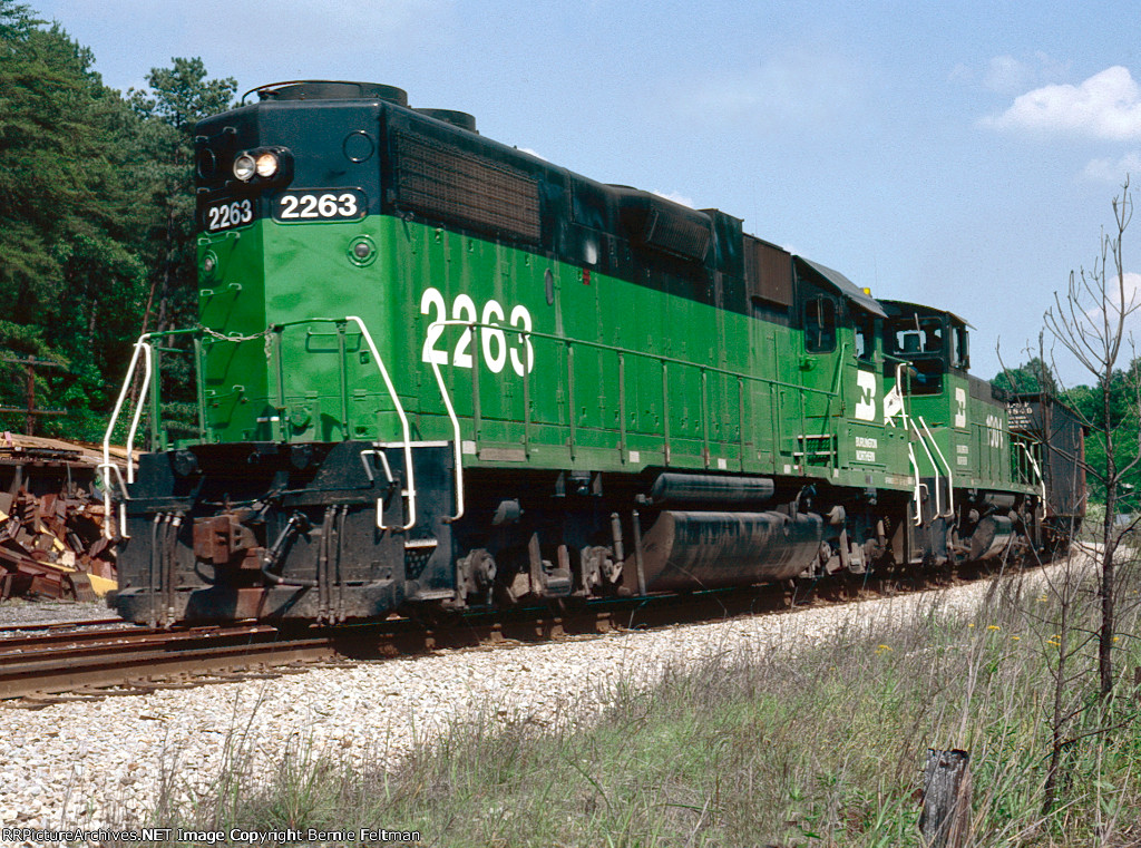 Burlington Northern GP38-2 #2263 and MP15DC #1004, leading the Jasper (AL) local, pass freight cars cleared from a derailment site