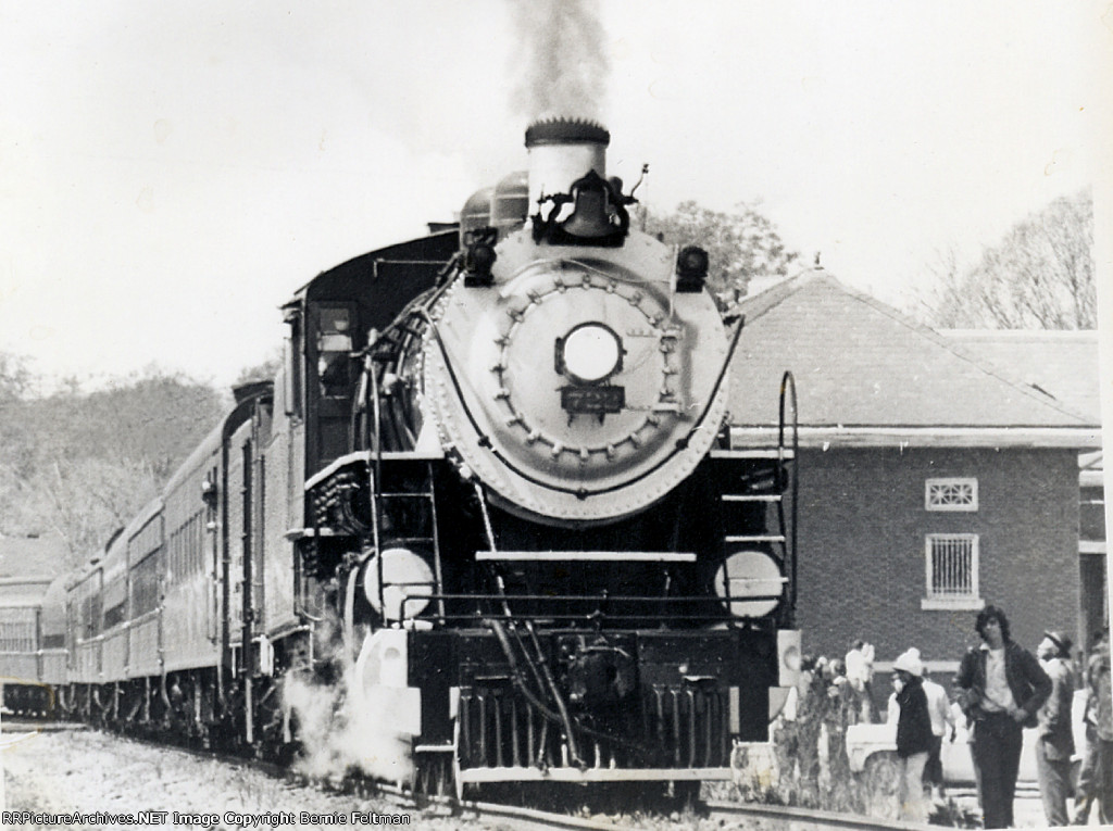 Southern Railway 2-8-0 #722 eases across the Western Railway of Alabama crossing and the crowd assembled around the depot as it prepares to make a service stop