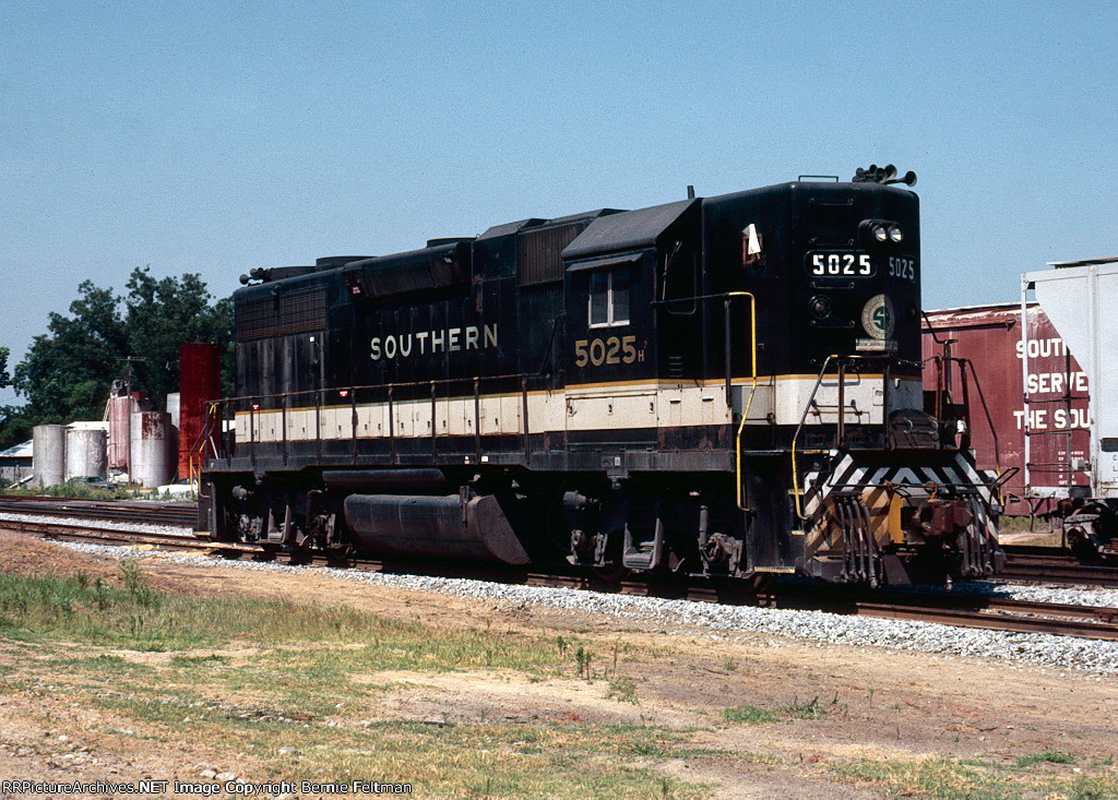 """Southern Railway GP38-2 #5025, working as Work Extra #5025 and flying white """"extra"""" class flags, is building its train for the run to Andalusia (AL) in the yard adjacent to the depot"""