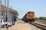 Fresh re-crewed BNSF grain train rolls past the depot