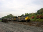 CSX #630 with a cut of trash cars up front heads west into the yard