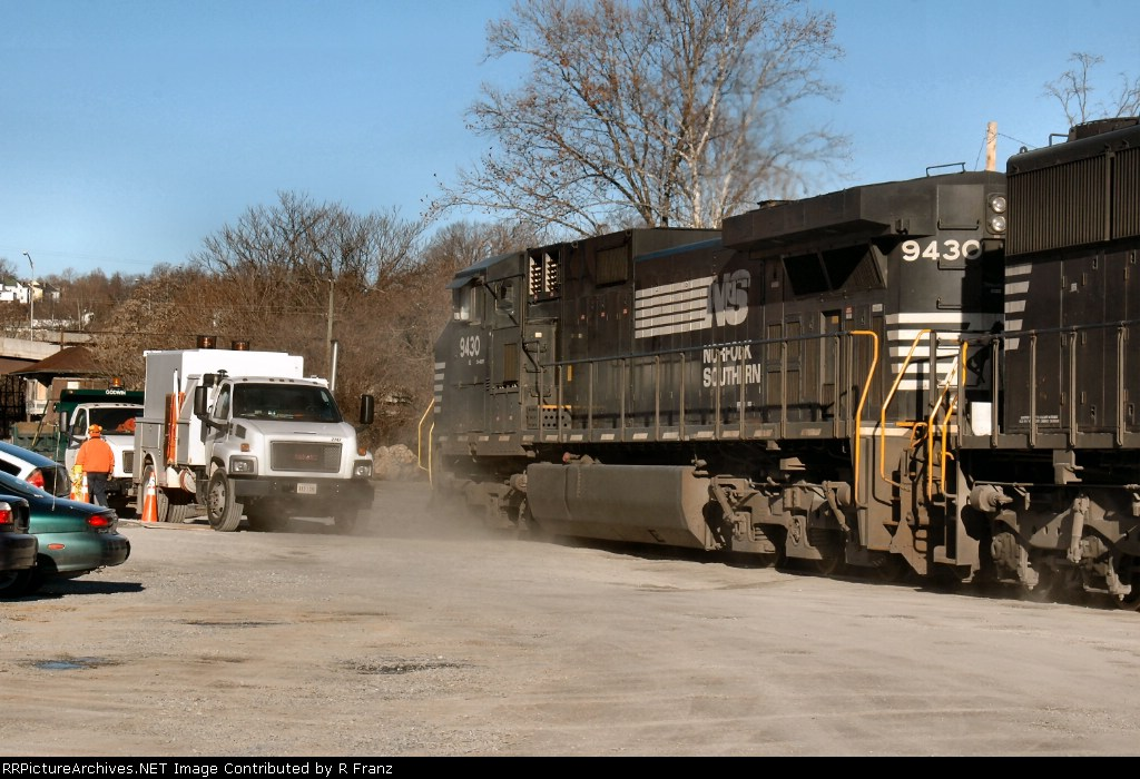 NS 9430 kicks up the dust as it rolls past city vehicles at the foot of 9th street