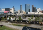 NS 332 with butthead in tow heads through the gulch with the Atlanta Skyline in the background