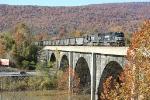 Eastbound coal across a big PRR stone bridge