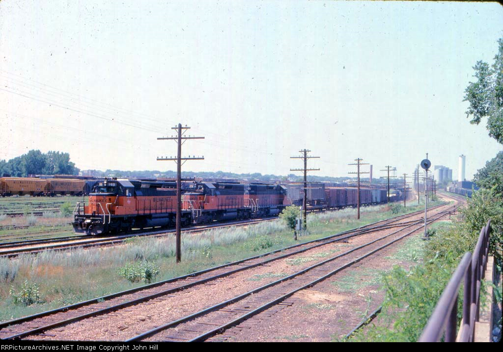 1014-25 Eastbound MILW freight passes Bass Lake Yard