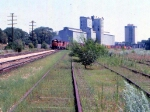 1014-18 Westbound MILW freight passes Bass Lake Yard & Burdick Elevators #1 & 2