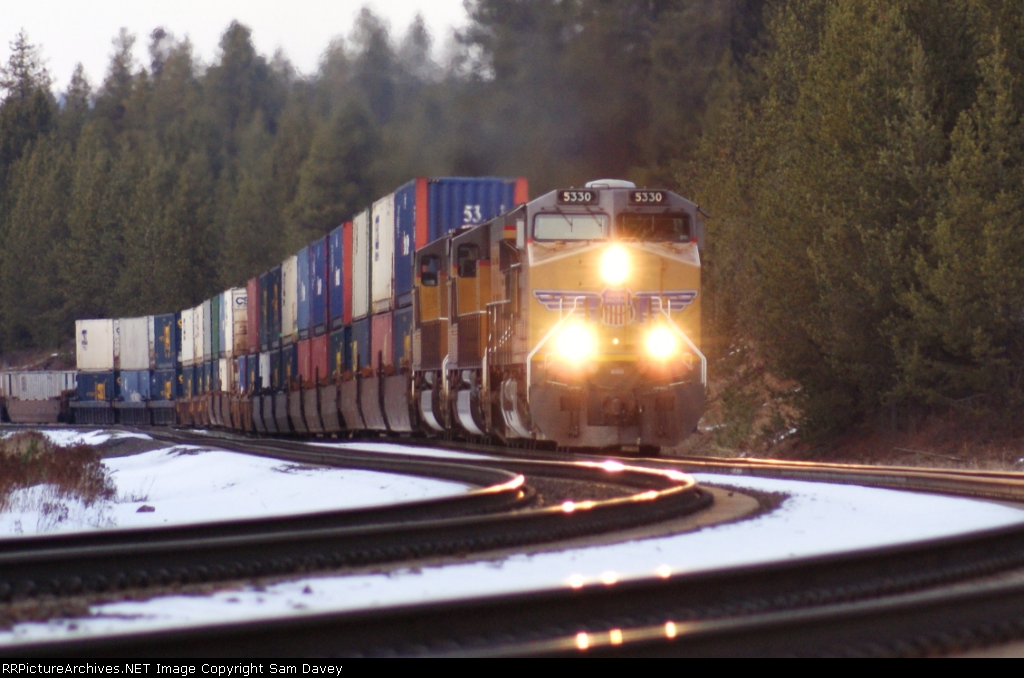 UP 5330 leads a colorfull stack train East.