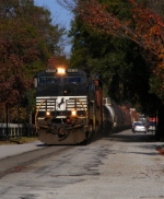 NS 155 kicks up dust and leaves in the middle of 6th Street