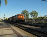 A BNSF train rapidly coming through the station